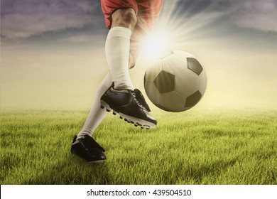 Foot of football player kicking a soccer ball on the green field, shot with sunlight in the morning