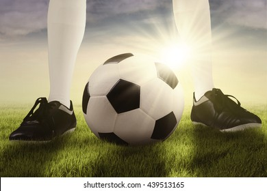 Foot of football player standing with a soccer ball at the field and ready for playing