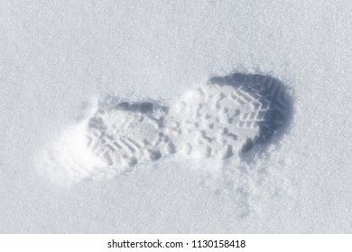 Foot imprint in white snow, close-up top view