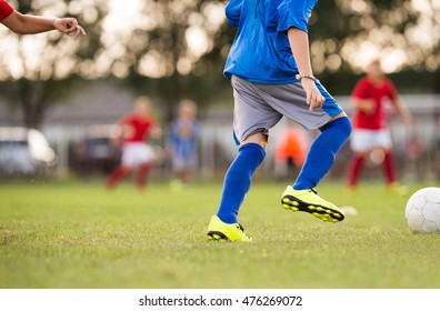Foot kicking soccer ball on the green field