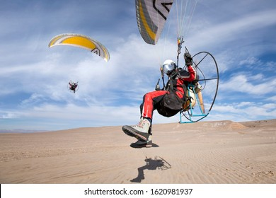 """Foot launch paramotor taking off or take off or landing in desert. Powered paraglider (""""PPG"""")"""