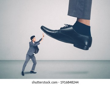 foot of leader or boss with authority huge trample on frightened employee with bullying, businessman in suite strong and defense, exploitation and dominance, scared and fight, business concept.