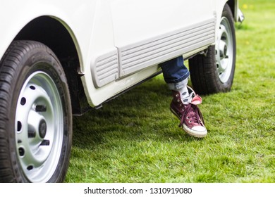 Foot and leg of a person coming out of the door of a car onto grass as the get ready to leave the car.