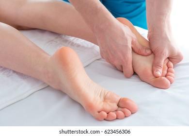 Foot and legs massage, alternative therapy, closeup studio shot