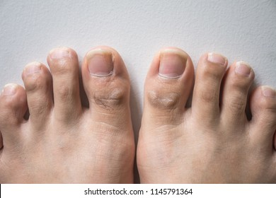 The foot and long nail toes on white concrete background. Long nails and dirty may cause fungal.