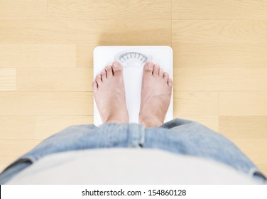 Foot of man standing on bathroom scale