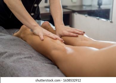 foot massage. Masseuse hands massaging women's legs on a massage table in a spa salon