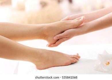 Foot massage in spa salon, closeup