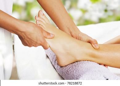 Foot massage in the spa salon in the garden