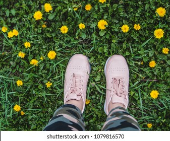 Foot on green grass with dandelions.