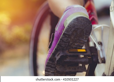foot on pedal of bicycle in park