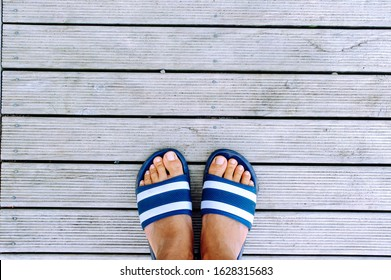 foot on the sandal on wooden background
