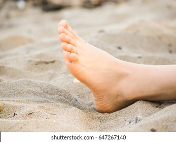 Foot of one unrecognizable caucasian person resting in sand, with no sand on foot