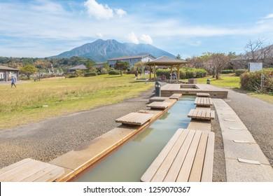 Foot onsen with Sakurajima mountain, sea and blue sky background,  Kagoshima, Kyushu, Japan