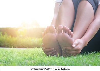 Foot Pain Leg of beauty woman sitting on the road park holding her feet and stretch the muscles in morning sunlight .Health care and spa concept.