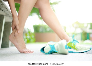 Foot Pain Leg of woman which runner athletic by running shoes sitting on grass in the park holding he feet and stretch the muscles in morning sunlight .Health care and spa concept