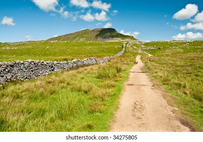 Foot path to Pen-y-Ghent with dry stone wall and blue sky and clouds