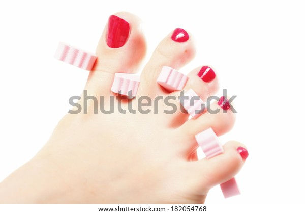 foot pedicure applying woman's feet with red toenails in toe separators white background