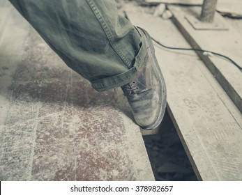 The foot of a person tripping on a gap between the floor boards in a room undergoing renovations