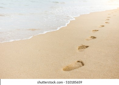 Foot print on sand at the beach background