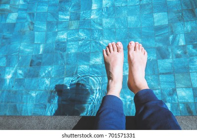 foot relaxing on the swimming pool