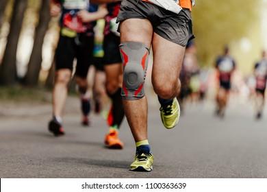 foot runner man in knee pads running ahead of group marathon runners