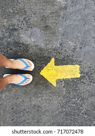 foot and sandals with yellow arrow on concrete road. subject is blurred.