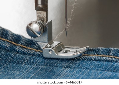 Foot of sewing machine on a denim pocket (closeup)