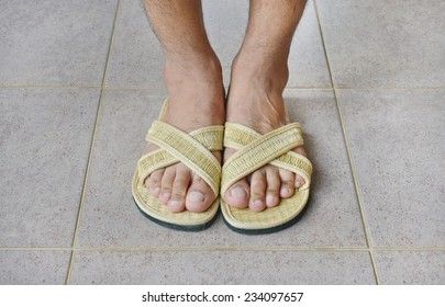 foot in slippers weave from natural material on tile