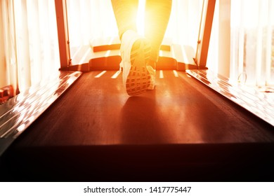 Foot sneakers of muscular woman walking on treadmill in fitness club. Out of focus legs shoes people workout on track treadmill at fitness gym. Lifestyle sport healthy concept.