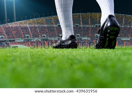 Foot of soccer player or football player walk on green grass ready to play match for the winner with stadium backgrounds.