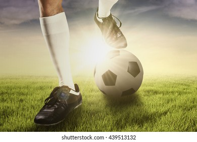 Foot of soccer player using a ball for training kick a ball, shot at the field at sunrise time