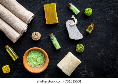 Foot spa cosmetics. Spa salt, pumice stone, soap and towel on black background top view