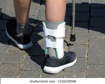 Foot with the splint, orthosis for leg. Person with cane walking after a broken or sprain legs. Orthopedic orthosis for immobilizing foot, treatment of injured