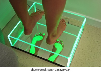 Foot step analysis on feet scanner - footprints visible in green light on plastic panel