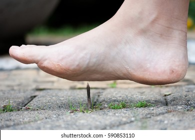 Foot stepping on rusty metal nail outdoors