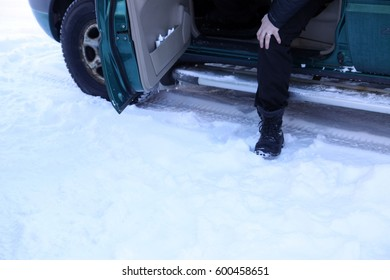 A foot stepping out of a car on the snowy ground
