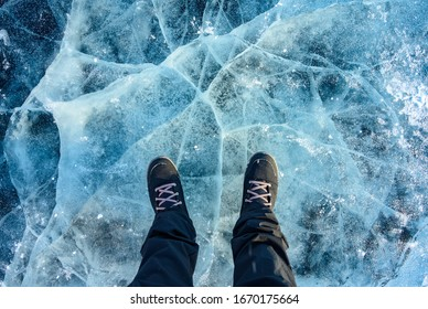 A foot of tourist standing on the cracks surface of frozen lake Baikal in the winter season of Siberia, Russia. Lake Baikal is the largest freshwater lake in the world and the world's deepest lake.