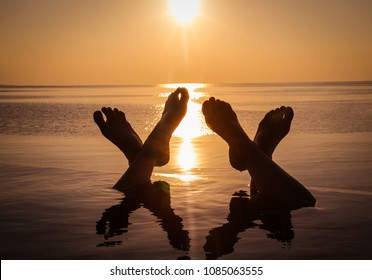 The foot of two people who enjoy the infinity pool in the sunset. Malsives.