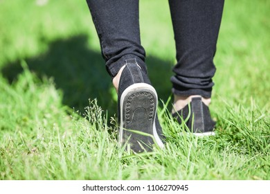 Foot walk with step out on green grass at sunny day, rear view at female legs with shoes and trousers