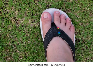 64c33e4d168a1 Foot wearing sandal on grass background