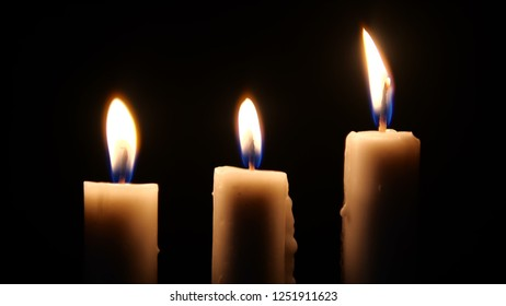 Footage of candles are lit in the darkness. Christmas
