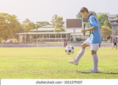 Football in action during a training, Low section portrait of unrecognizable teenage boy kicking ball during football practice in field , focus on football ball lying on grass