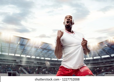 The football african player in motion on the field of stadium at day. The professional football, soccer player and human emotions concept. The win, winner, victory concept