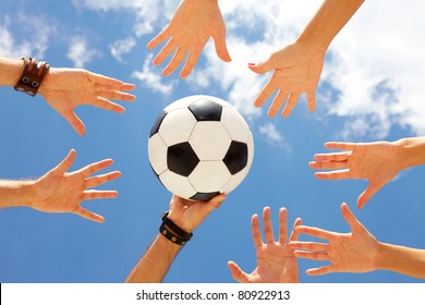 A football ball in circle of hands