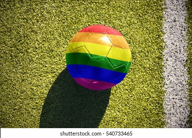 football ball with the gay rainbow flag lies on the green field near the white line