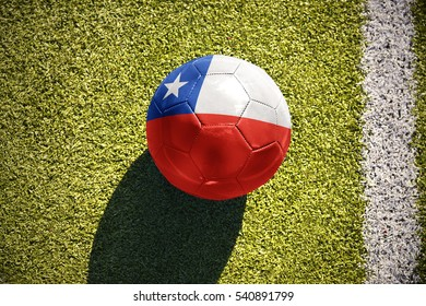 football ball with the national flag of chile lies on the green field near the white line