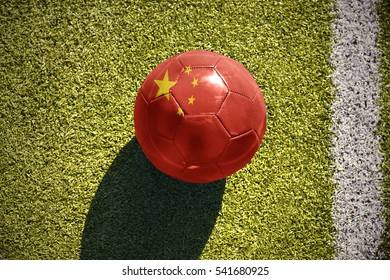 football ball with the national flag of china lies on the green field near the white line