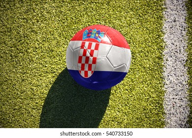 football ball with the national flag of croatia lies on the green field near the white line
