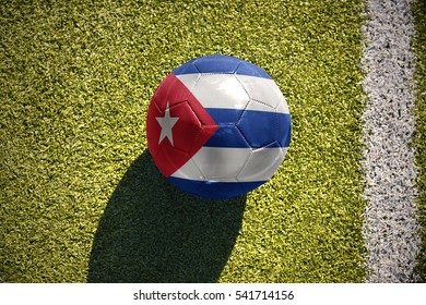 football ball with the national flag of cuba lies on the green field near the white line